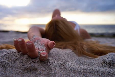shallow photography of woman holding sand during daytime