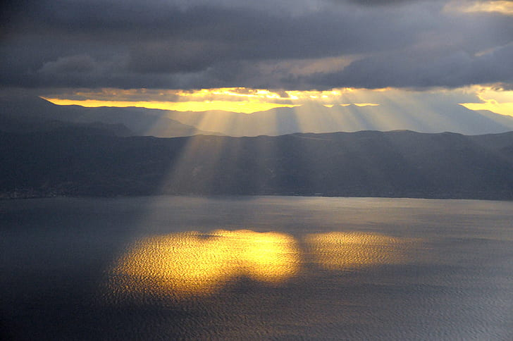 sun rays on body of water during dark clouds
