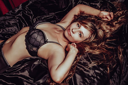 woman in black bra lying on black textile