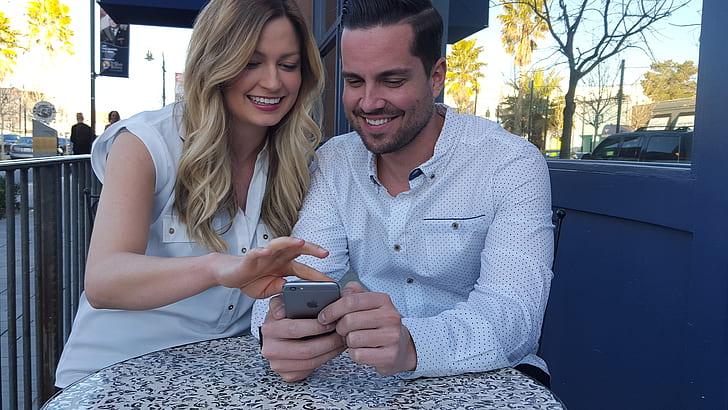 man using iPhone beside woman sitting near road