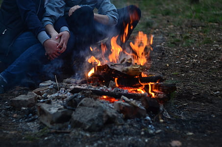 two person holding each other facing towards bone fire