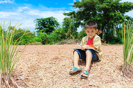 boy holding pen and book while sitting on ground in middle of trees