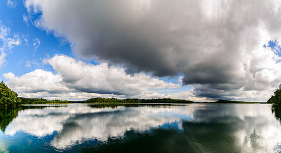 reflective photography of clouds and body of water