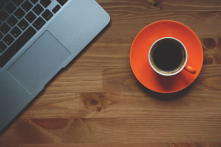 cup of coffee beside gray laptop on brown wooden desk
