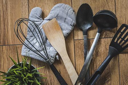 assorted kitchen utensils on brown wooden top