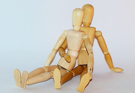 two brown jointed wooden dolls
