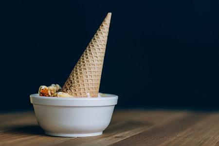 brown ice cream cone dipped on white ceramic bowl
