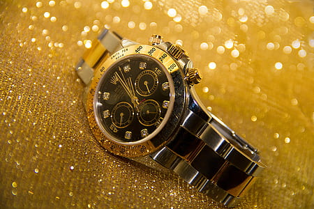 round gold-colored and black Rolex analog watch with link band