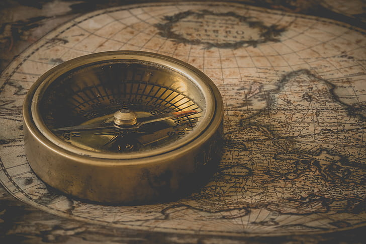 photo of gold-colored compass on brown map