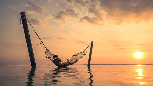 man lying in hammock above body of water during sunset