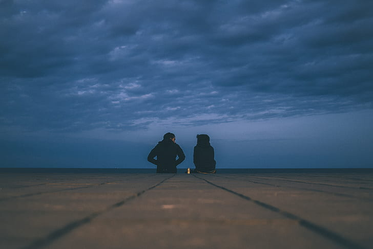 silhouette of two person sitting on ground under gloomy skies