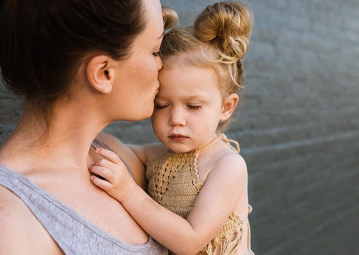 woman carrying girl kissing on forehead