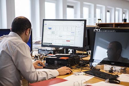 man in grey collared shirt sitting down facing flat screen computer monitor