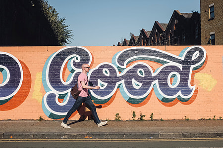 man in pink top, blue jeans, and white low top sneakers walking on street