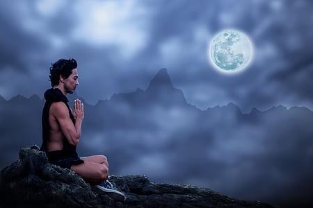 man sitting on mountain meditating