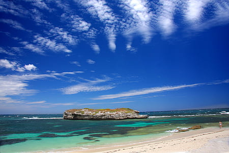 islet under blue sky and white clouds