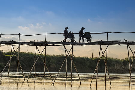 silhouette of person on top of wooden bridge during daytime