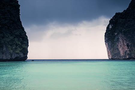 blue body of water under grey cloudy sky