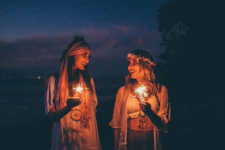 Two women smile at sunset holding sparklers