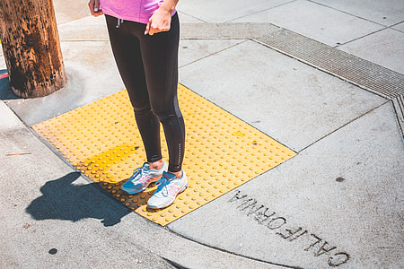 Young Female Jogger Waiting at the Edge of a Zebra Crossing