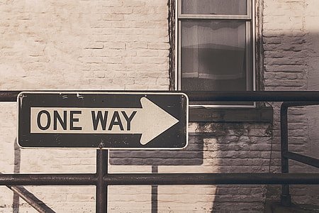 black and white One Way signboard
