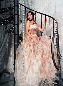woman in white, red, and brown strapless dress sitting on black metal spiral stairs