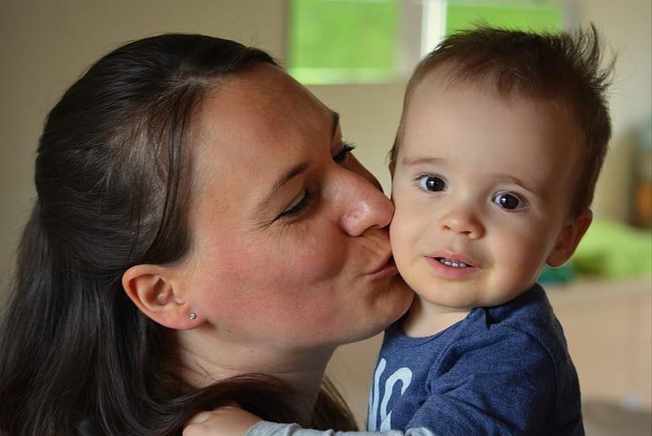 woman kissing toddler