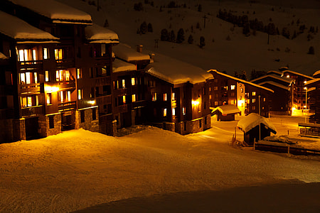 lighted village houses surrounded of snow covered field during nighttime