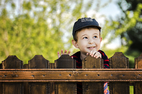 boy wearing black cap standing behind wooden fence