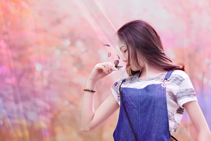 woman with blue denim top and white striped shirt holding grey butterfly