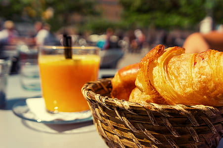 basket of baked bread near clear drinking glass