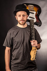 man wearing black crew-neck t-shirt and hat holding sunburst electric guitar