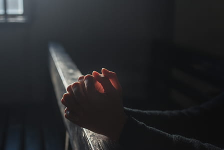 person praying hands selective focus photographyt