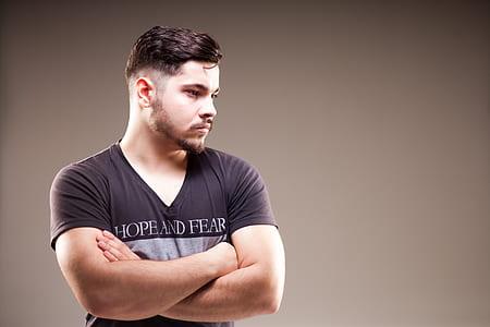 man wearing black shirt against gray wall