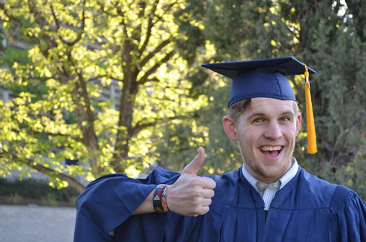 Royalty-Free photo: Man in mortarboard and academic dress showing ...