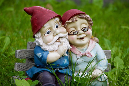 male and female dwarf seating on gray bench chair figurine