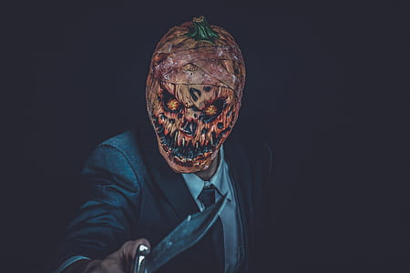 person in black coat holding silver knife wearing orange scary mask