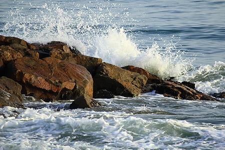 body of water beside brown rocks
