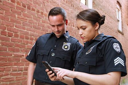 police woman holding phone near man