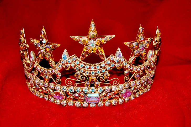 gold-colored crown with assorted-color gemstones on red textile