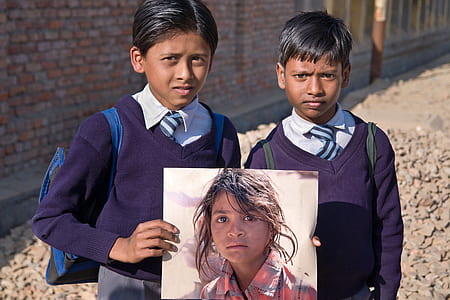 boy in purple sweater holding photo of a girl