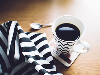 white ceramic cup with coffee beside spoon