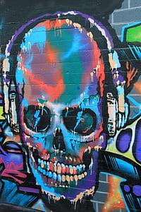 multicolored graffiti art of skull wearing headphones