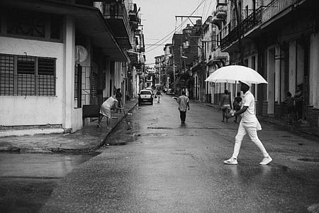 man wearing white suit holding white umbrella selective grayscale photo