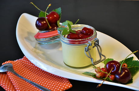 photo of air-tight jar filled with red cherry in white boat bowl