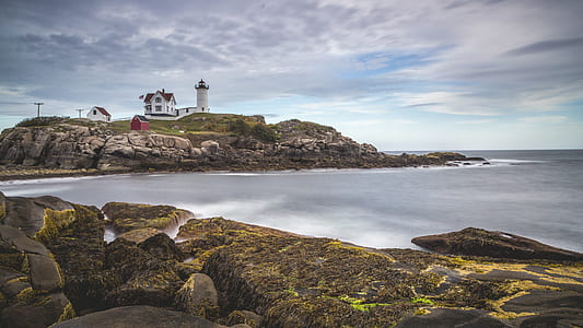 long exposure brown stones with lighthouse and building
