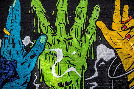 Street art depicting vibrantly coloured hands captured on a brick wall
