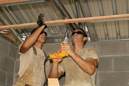 man wearing gray crew-neck t-shirt using yellow corded hand drill