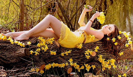 woman in yellow dress laying on tree while holding flowers