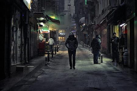 man in black hoodie walking beside concrete building at nighttime